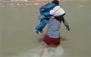 معلمی که با فداکاری دانش آموز را بر روی دوش خود از رودخانه عبور میدهد