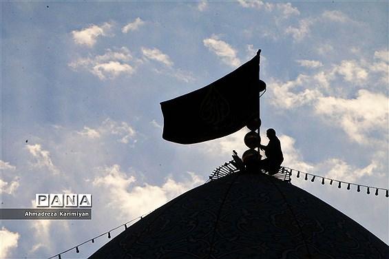 آیین سیاهپوشان حرم مطهر احمدابن موسی(ع) و تعویض پرچم گنبد با پرچم عزا