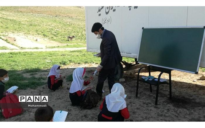 معلمی که در منطقه عشایری ایلِک در فضای باز مشغول تدریس است