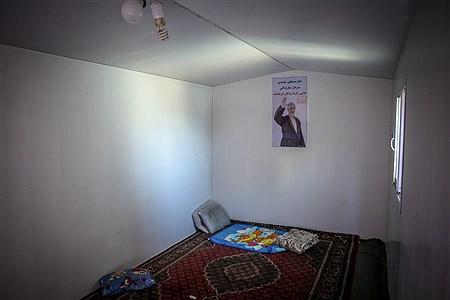 داخل یکی از کانکس های مردم زلزله زده شهر سرپل ذهاب که بر روی دیوار عکسی از مسئولین کرمانشاه به صورت بنر نصب کرده است | Ali Sharifzade